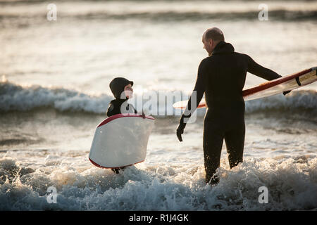 Mid adult man and his young son having a conversation while standing in shallow water holding their boards at the beach. - Stock Photo
