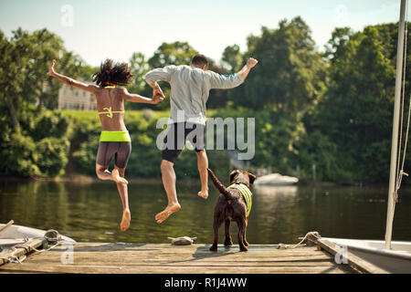 Happy young couple jumping off of a jetty. - Stock Photo