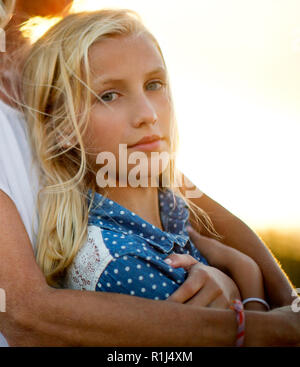 Portrait of a teenage girl leaning against her mother. - Stock Photo