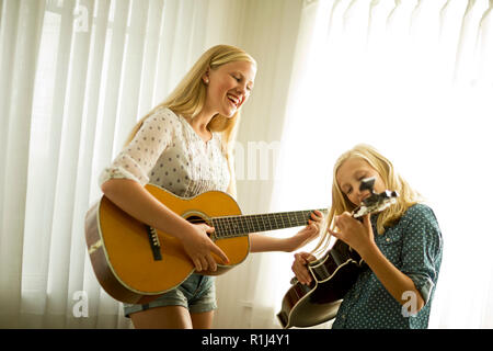 Happy teenage girls playing guitar together. - Stock Photo