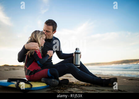 Affectionate father tenderly kisses his young daughter on the head as they relax on the beach after a long day. - Stock Photo