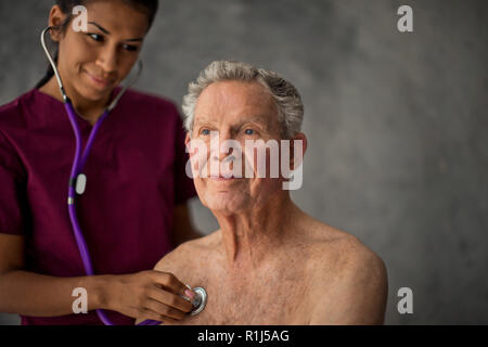Happy young nurse listening to a senior patient's heartbeat. - Stock Photo