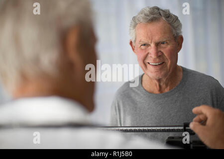 Smiling mature man watches his doctor set up scales before a medical examination. - Stock Photo