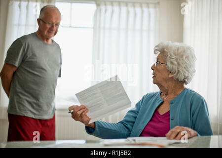 Elderly woman asks her worried husband about a bill they have received. - Stock Photo