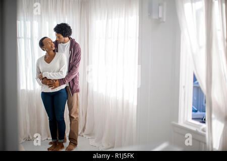 Happy young man embracing his beautiful partner. - Stock Photo