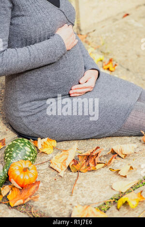 Pregnant woman with gourds and autumn leaves - Stock Photo