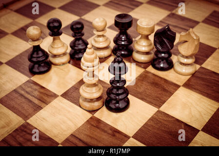 Black and white chess pieces on chessboard - Stock Photo