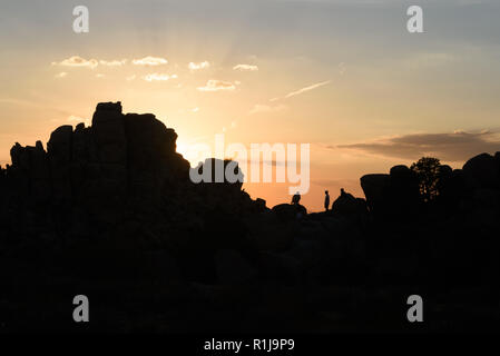 Hikers climbing the boulders in silhouette at Joshua Tree National Park. - Stock Photo