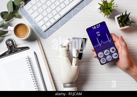 partial view of businessman with cyborg hand holding credit card and using smartphone with medical application on screen at table with coffee cup in o - Stock Photo