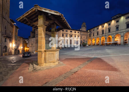 Arezzo, Italy. Old well located on Piazza Grande square at dusk - Stock Photo