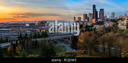 Seattle downtown skyline and skyscrapers  beyond the I-5 I-90 freeway interchange at sunset in the fall with yellow foliage in the foreground view fro