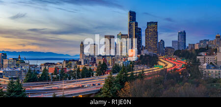 Panorama of Seattle downtown skyline beyond the I-5 I-90 freeway interchange at sunset with long exposure traffic trail lights from Dr. Jose Rizal or