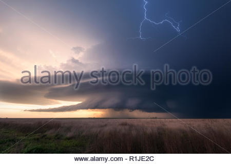 Cloud-to-cloud lightning during sunset with a supercell over the fields of Leoti, Wichita County, Kansas, USA on May 21st 2016 - Stock Photo