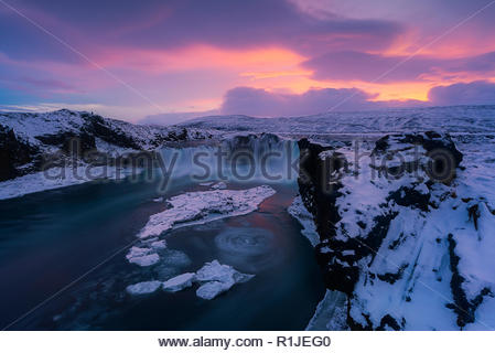 Sunset over Godafoss waterfall at ice and snow in winter, highlands, Iceland - Stock Photo