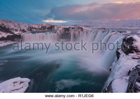 Evening light over Godafoss waterfall at ice and snow in winter, highlands, Iceland - Stock Photo