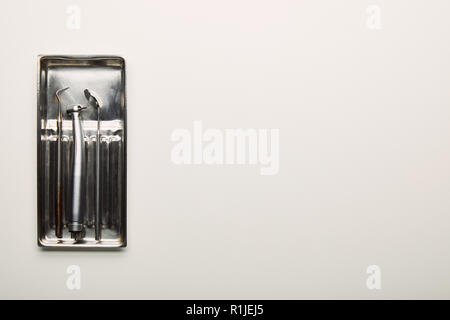top view of stainless dental instruments in container on white tabletop - Stock Photo