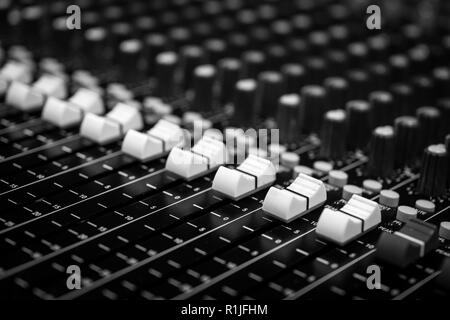Low level view of Faders on a Professional Audio Sound Mixing Console at music festival, black desk and white Faders - Stock Photo
