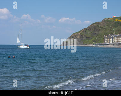 UK Weather: Aberystwyth, Ceredigion, West Wales Thursday 12th May 2016. Tempretures reach 23 dergees. A sail boat passes by two swimmers in the sea of - Stock Photo