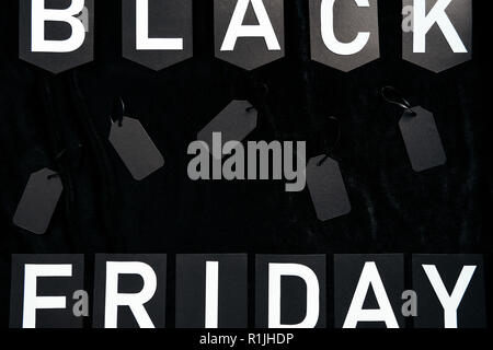 top view of black friday lettering and blank price tags on black background - Stock Photo