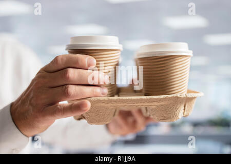 Businessman carrying coffee take out disposable cups for office meeting - Stock Photo