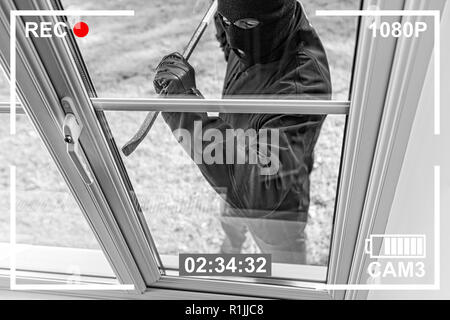 CCTV view of burglar breaking in to home through window with crowbar - Stock Photo