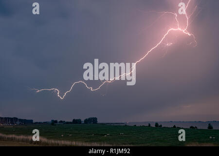 Cloud to cloud lightning in a severe thunderstorm over the province of Zeeland, The Netherlands. - Stock Photo