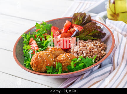 Meatballs, salad of tomatoes and buckwheat porridge on white wooden table. Healthy food. Diet meal. Buddha bowl. - Stock Photo