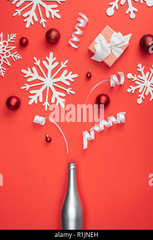 top view of present, silver bottle, red christmas toys, white ribbons and decorative snowflakes arranged isolated on red - Stock Photo