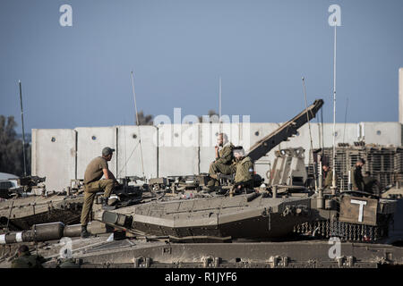 Israel. 13th Nov, 2018. Israeli soldiers sit on top of Merkava battle tanks stationed along the Israeli-Gaza border. According to Israeli army spokesman, Palestinian militants has launched nearly 400 rockets and mortar shells from the Gaza Strip into Israel, who has later responded by airstrikes on more than 100 military targets in response. Credit: Ilia Yefimovich/dpa/Alamy Live News - Stock Photo