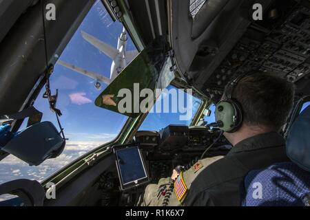U.S. Air Force Maj. Bartholomew D. Murphy, a C-17 Globemaster III pilot with the 732nd Airlift Squadron, 514th Air Mobility Wing, maneuvers in to be refueled by a KC-10 Extender crewed by Reserve Citizen Airmen with the 514th's 78th Air Refueling Squadron during a joint training mission with the 514th Aeromedical Evacuation Squadron (AES), 45th AES, and the 439th AES over the United States Oct. 5, 2018. The 514th is an Air Force Reserve Command unit at Joint Base McGuire-Dix-Lakehurst, N.J. The 45th and the 439th AES are Air Force Reserve Command units from MacDill Air Force Base, Fla., and We - Stock Photo