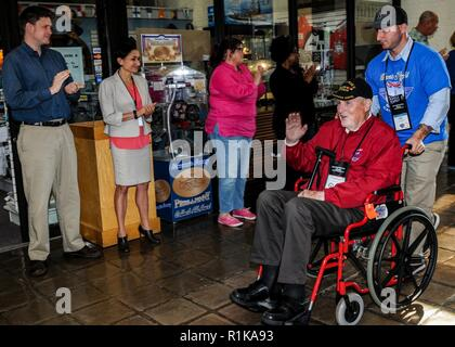 WASHINGTON (October 12, 2018) Thomas O'Brien, a World War II veteran who served in the U.S. Navy as a Gunner's Mate 3rd Class, is greeted by Sailors and Civilians as he is pushed by his grandson, Daniel Paul Thomas O'Brien, as they enter the National Museum of the U.S. Navy during an Honor Flight visit. Naval History and Heritage Command (NHHC) hosted the Honor Flight Bay Area (California) as part of the Navy's 243rd Birthday celebration. NHHC, located at the Washington Navy Yard, is responsible for the preservation, analysis, and dissemination of U.S. naval history and heritage. - Stock Photo