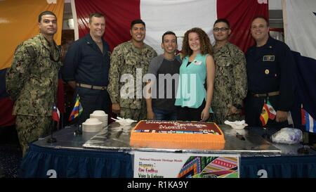 NORFOLK, Va. (Oct. 9, 2018)- Sailors from the amphibious assault ship USS Bataan (LHD 5) pose for a photo during Bataan's Hispanic Heritage Month celebration, (left to right) Chief Aviation Boatswain's Mate Mark Hernandez, Executive Officer, Capt. Greg Leland, Lt. Mark Rodriquez, Gunner's Mate Seaman Johnny Castroosorio, Mikaela Juday, Culinary Specialist First Class Ernesto Lopez and Command Master Chief Ryan Lamkin. Bataan is in a scheduled maintenance availability at BAE Ship Repair. - Stock Photo