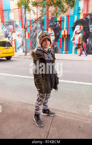 Nine year old boy in front of the 27 club mural by Eduardo Kobra,170 Forsyth Street & Rivington Street, New York City, United States of America. - Stock Photo