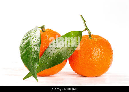 Tangerines with leaves and water drops on white wooden background, closeup - Stock Photo