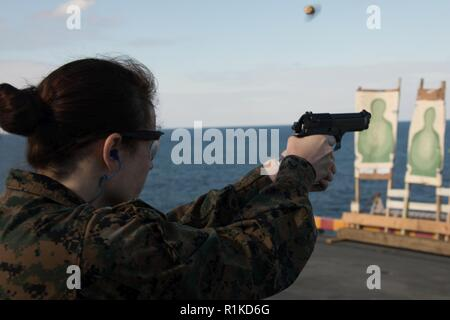 LT Sierra R. Nichols, a medical planner with the 31st Marine Expeditionary Unit fires an M9A1 9 mm service pistol during pistol qualification on the flight deck of the amphibious assault ship USS Wasp (LHD 1), underway in the East China Sea, Oct. 15, 2018. Nichols, a native of Tampa, Florida, graduated from the University of South Florida in January 2016; she comissioned in March 2014. Marines undergo yearly rifle and pistol qualifications to stay proficient in their weapon skills and handling. The 31st MEU, the Marine Corps' only continuously forward-deployed MEU, provides a flexible force re - Stock Photo