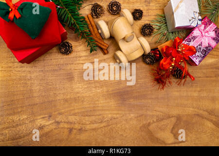 Christmas background. Christmas presents gifts, toy wooden machine and festive decorations on wooden background retro style Top view with copy space. - Stock Photo