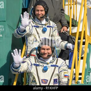 Expedition 57 Flight Engineer Nick Hague of NASA, top, and Flight Engineer Alexey Ovchinin of Roscosmos, wave farewell prior to boarding the Soyuz MS-10 spacecraft for launch, Thursday, Oct. 11, 2018 at the Baikonur Cosmodrome in Kazakhstan. Hague and Ovchinin will spend the next six months living and working aboard the International Space Station. - Stock Photo
