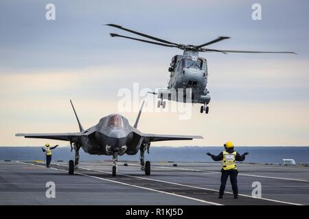 NORTH ATLANTIC (Oct. 13, 2018) An F-35 Lightning II assigned to the F-35 Integrated Test Force at Naval Air Station Patuxent River, Md., conducts the first ever shipborne rolling vertical landing (SRVL) aboard the Royal Navy aircraft carrier HMS Queen Elizabeth (R08). - Stock Photo