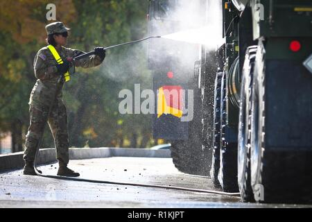 U.S. Army Pfc. Lara Bulatao, a native of San Diego, California, assigned to Indian Forward Support Company, 2nd Battalion 5th Cavalry Regiment, 1st Armored Brigade Combat Team, 1st Cavalry Division power-washes an M978 HEMTT fueler during a wash rack operation, Mihail Kogalniceanu Air Base in Romania, October 16, 2018. These Soldiers are deployed to Europe in support of Atlantic Resolve, an enduring training exercise between NATO and U.S. Forces. - Stock Photo