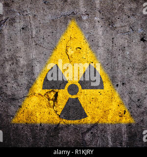 Radioactive (atomic ionizing radiation) danger warning symbol in triangular yellow shape painted on a massive cracked concrete cement wall with and da - Stock Photo