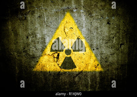 Radioactive (atomic nuclear ionizing radiation) danger warning symbol in triangular yellow shape painted on a massive cracked concrete cement wall wit - Stock Photo
