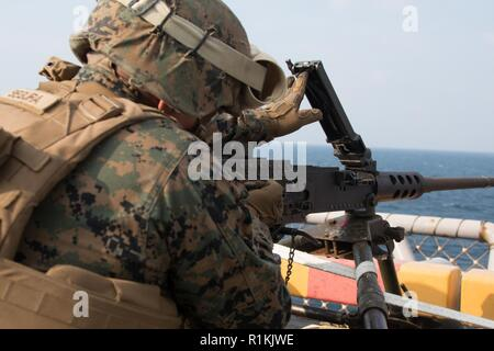 Cpl. Pedro Segura, a military policeman with Weapons Company, Battalion Landing Team, 2nd Battalion, 5th Marines, reloads an M2 .50-caliber Browning machine gun during marksmanship training aboard the amphibious assault ship USS Wasp (LHD 1), underway in the East China Sea, Oct. 17, 2018. Segura, a native of Los Angeles, graduated from Clevelend High School in June 2013; he enlisted October 2014. Weapons Company Marines conducted this training to sustain skills with automatic weapon systems throughout the fall patrol. The 31st Marine Expeditionary Unit, the Marine Corps' only continuously forw - Stock Photo