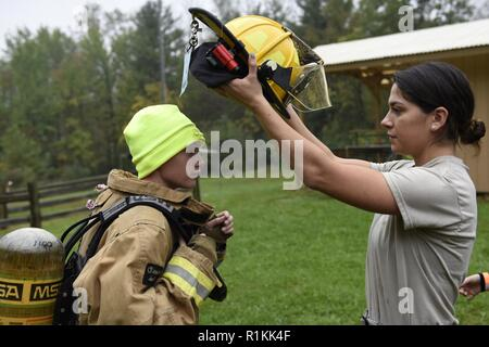 U.S. Air Force Airman 1st Class Brianna Espino, a firefighter assigned to the 180th Fighter Wing, Ohio Air National Guard, helps Noah Milks, a Boy Scout from Troop 263 out of Toledo, Ohio, get dressed in a firefighter's suit during the Camp Frontier  50th Anniversary camporall Oct. 6, 2018 in Pioneer, Ohio.  Airmen from the 180th Fighter Wing, Ohio Air National Guard strive to give more to the community than they receive. - Stock Photo