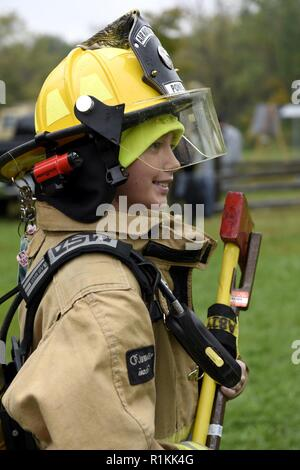 Noah Milks, a Boy Scout from Troop 263 out of Toledo, Ohio, wears a firefighter's suit during the Camp Frontier  50th Anniversary camporall Oct. 6, 2018 in Pioneer, Ohio.  Airmen from the 180th Fighter Wing, Ohio Air National Guard strive to give more to the community than they receive. - Stock Photo