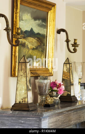 Ornaments by painting on mantelpiece - Stock Photo