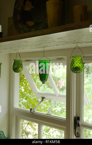 Green candle holders hanging by window - Stock Photo