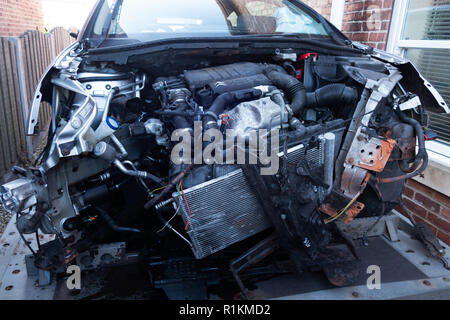 Engine and engine bay and written off front end in crash damaged citroen c4 car on a recovery trailer - Stock Photo