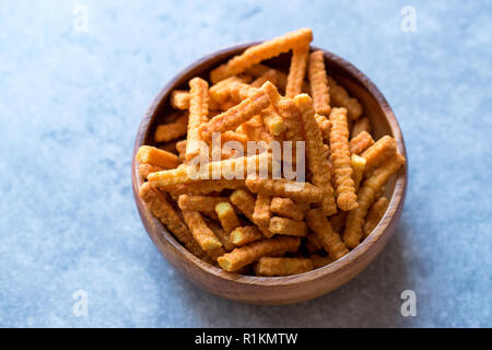 Orange Cheese Flavored Corn Snacks in Stick Shape / Roasted Chips or Salty Crackers in Wooden Bowl. Organic Roasted Snacks. - Stock Photo