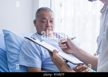 doctor filling up medical form at clipboard while standing and talking to old patient on bed in hospital - Stock Photo