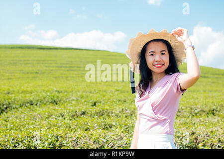 portrait of  beautiful Thai woman wearing hat and posting at green tea filed with blue sky - Stock Photo